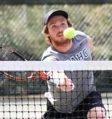 Senior Jackson Varney returns the ball during doubles competition Saturday in Moscow.